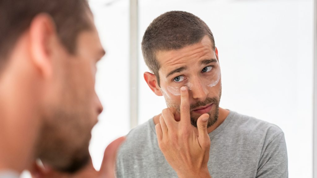 Man applying moisturiser under eyes